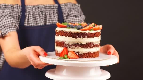 Cukrász lány tart két keze finom torta.
