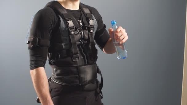 Přizpůsobit muž nosí elektro stimulace oblek pít vodu po tréninku.