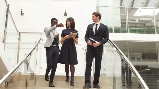 Boldog többnemzetiségű üzletemberek séta le a lépcsőn együtt digitális tabletta.