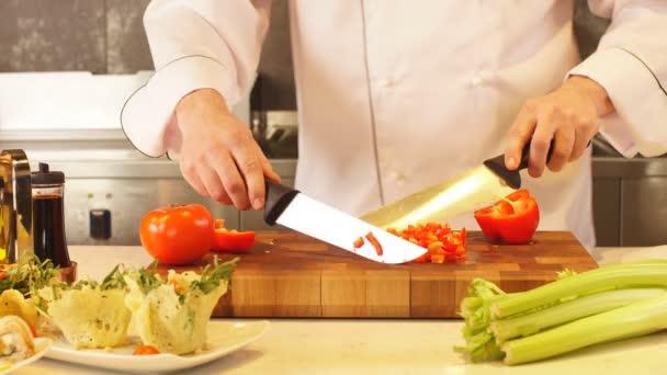 Muž v kuchyni sekání zeleniny.