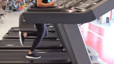 Portrait of sportive brunette woman jogging exercising on treadmill in gym.