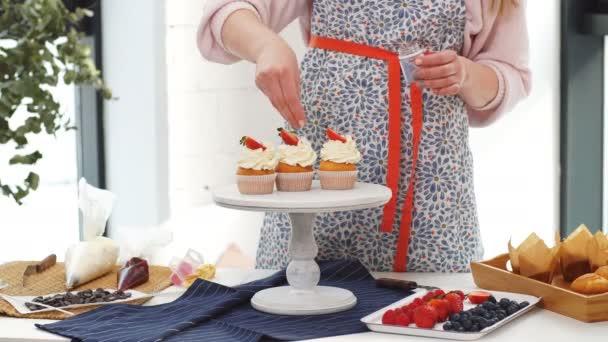 ženské baker zdobí košíčky.