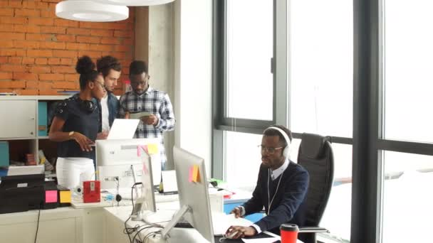 Businesslike cooperation among African and Caucasian office workers.