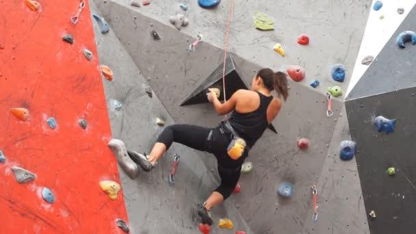 Krásná mladá dívka sportovní lezení na vnitřní lezecká stěna.