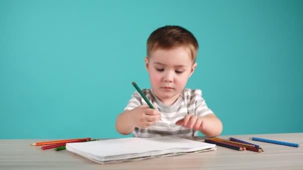 Roztomilý chlapeček kreslení s tužky v albu na modrém pozadí