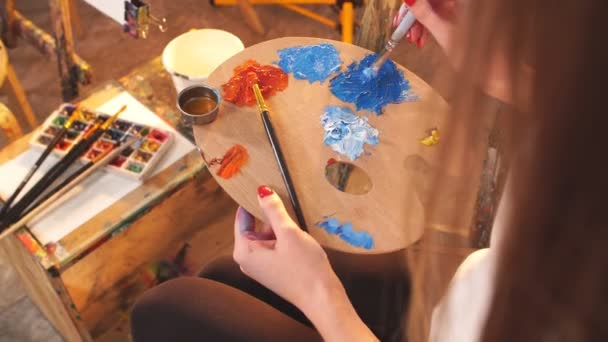 Woman artist holding palette with blue and red oil coloures and painting picture close-up.