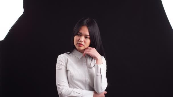 Schöne asiatische Frau mit langen Haaren posiert im Studio auf schwarzem Hintergrund.