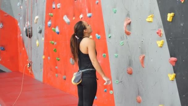 Egy nő, aki sziklát mászik a mesterséges falon. Aktív életmód és sziklaképződés.