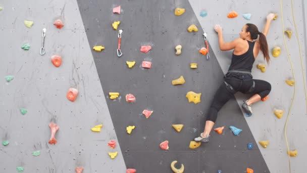 Csinos, fiatal sportos lány egy fedett sziklamászó falat mászni.