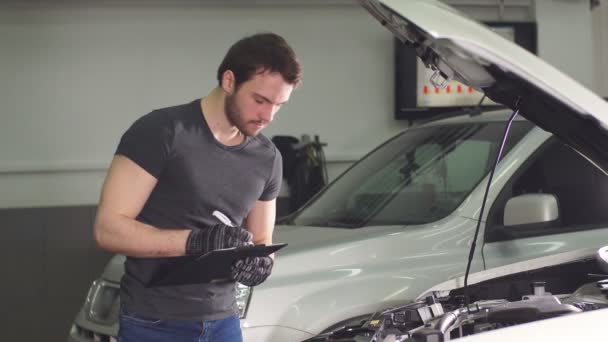 Auto Repair Nearby >> Car Mechanic Is Standing In An Auto Repair Shop Near Automobile With Open Hood And Making Notes