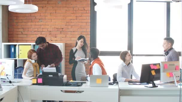 mladí to specialista diskutují o data v kanceláři s prosklenými stěnami.
