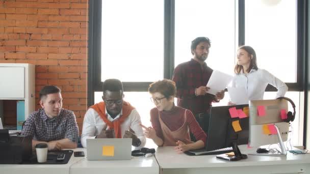 Young It Specialist diskutieren Daten im Büro mit Glaswänden.