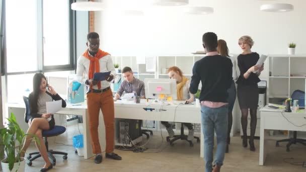 Nadnárodní mladí podnikatelé v neformálním oblečení spolupracují společně uvnitř.