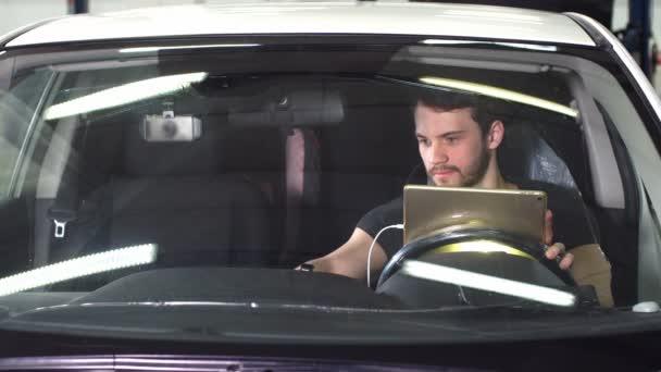 Mechanic sitting in car doing diagnostics on digital tablet.