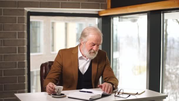 Schöne Reife Geschäftsmann in klassischen Anzug und Brillen, Kaffee zu trinken, während der Arbeit in seinem Büro.