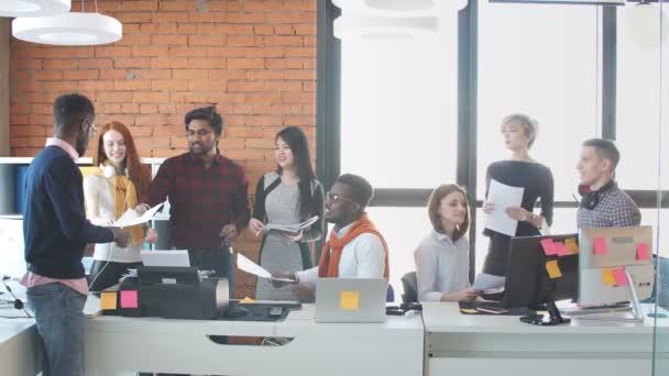 mladí ambiciózní lidé v neformálním oblečení pracují s papírem.