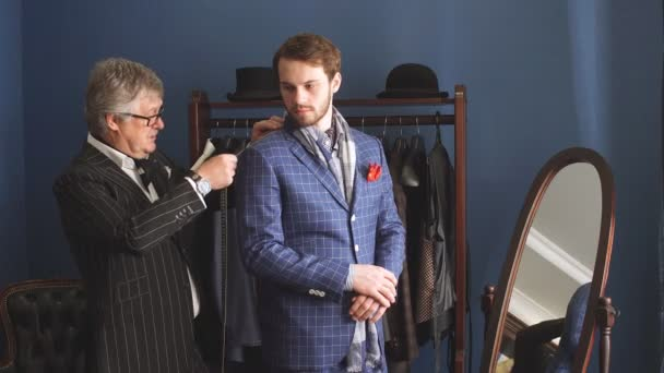 Tailor with client in atelier. Sewing custom made suit.