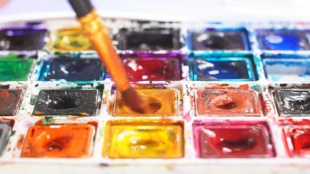Kreslířce míchání olejové barvy na paletě, drží v ruce