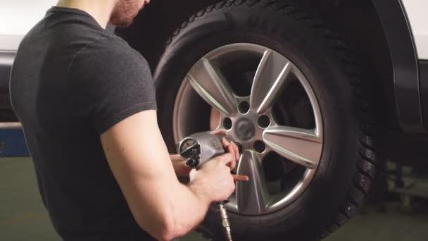 Automechaniker wechselt Autorad in Autowerkstatt.