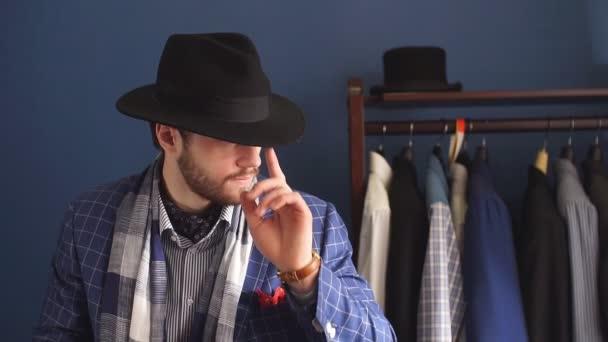 Elegantní muž v módní oblek a klobouk pózuje v ateliéru s nápojem