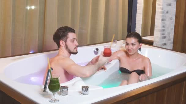 Nádherný pár uvolňující a pít koktejl v vířivka v hotelu.