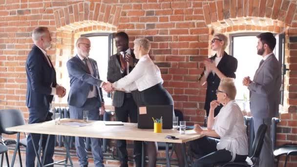 Egy csoport üzletember az irodában gratulál kollégájának, aki asztalnál ül és laptopon dolgozik..