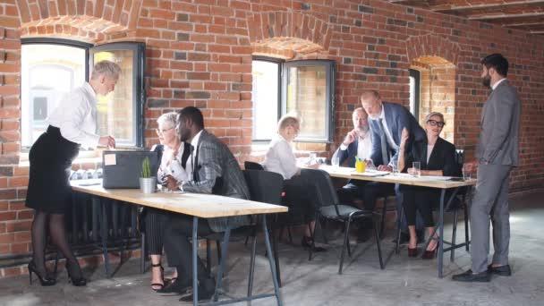 Diversi vecchi e giovani lavoratori dellufficio si riuniscono parlando di ridere di progetto online che lavorano insieme al meeting aziendale di gruppo.
