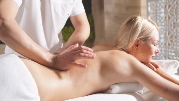 Ruce profesionální masérky terapeut dělá masáž na zádech krásné blondýny