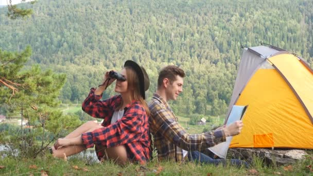 Loving couple sitting on the top mountain enjoying view of nature at sunny day in summer.
