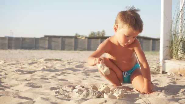 kleiner blonder Junge spielt mit dem Sand an einem unberührten Strand