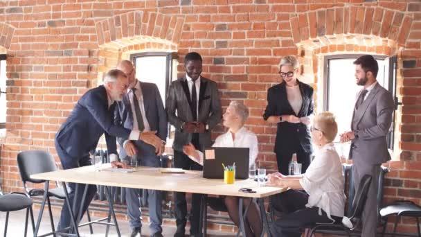 Gruppe älterer Geschäftsleute gratuliert Kollegin, die am Tisch sitzt und am Laptop arbeitet.