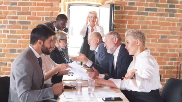 Führungspersönlichkeit mit Kopfschmerzen beobachtet ihre Mitarbeiter, die Finanzdokumente analysieren