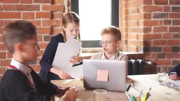 Zázvorový chlapec dává rady sekretářce, zatímco jeho kolega dělá poznámky v popředí