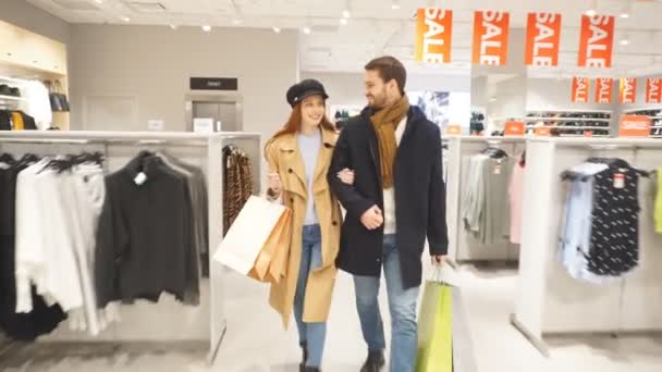 Young happy couple carries bags with purchases. Slow motion.