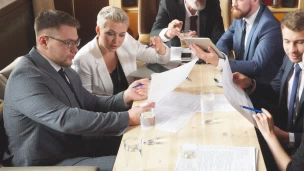 Businesspeople discussing issues together in small conference room during meeting at bright office