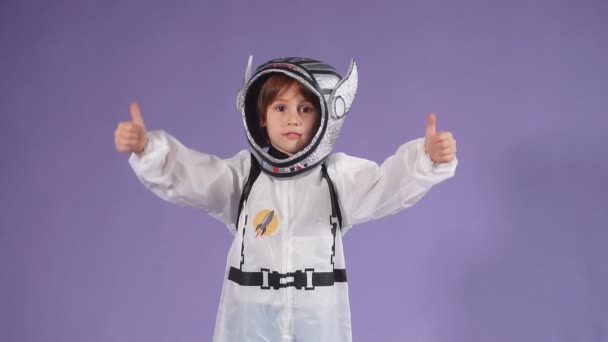Little astronaut kid boy wearing white protective suit and helmet over purple background