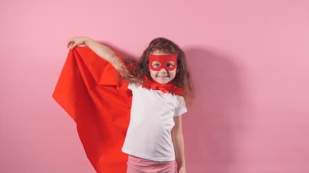Portré erős kislány szuperhős köpenyben és maszkban