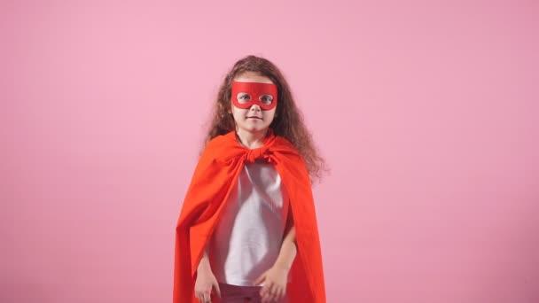 Gyönyörű kis göndör lány visel piros hős ruha és maszk elszigetelt rózsaszín háttér