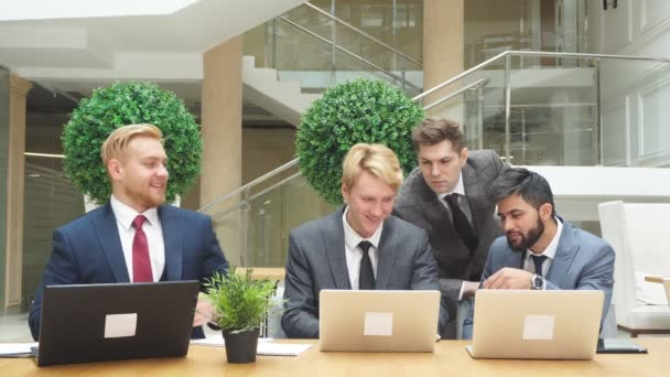 Group of multi national young men looking at laptop while discussing new project, new deal.