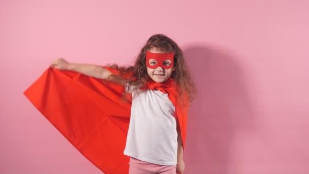 Portré magabiztos mosolygós gyerek szuperhős visel piros köpeny és maszk a szemen képzeli magát, mint egy hős