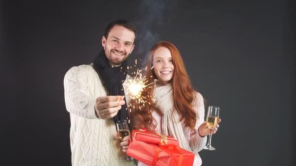 Boldog karácsonyt! Boldog pár ünnepli az újévet pezsgős poharakkal és csillagszórókkal