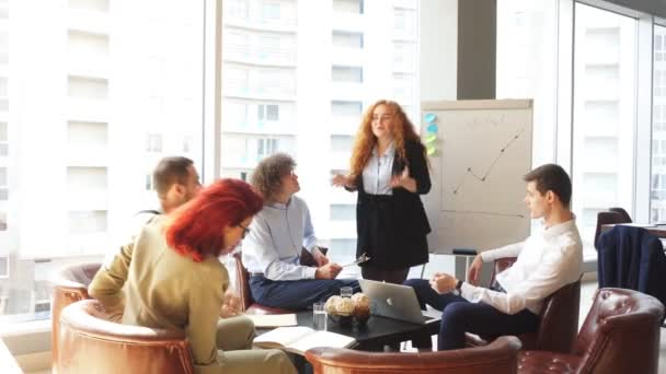 Female business consultant reading a lecture for group of young professionals