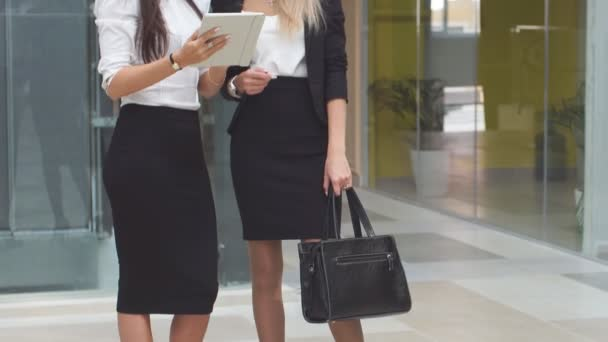 Two female business partners communicate in lobby of modern office center