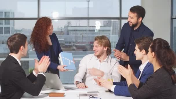 Group of businessmen in office congratulate colleague, they clap and smile