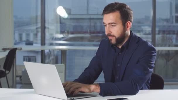 Hezký muž pracující pomocí notebooku při pohledu na obrazovce monitoru