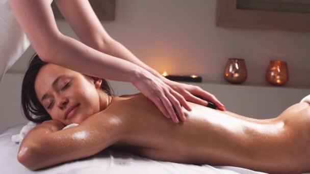 Lázeňská masáž těla. Žena si užívá relaxační masáž těla v luxusním lázeňském centru.