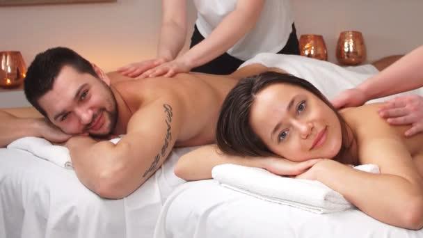 Krásný pár si užívá relaxační masáž v moderním lázeňském centru.