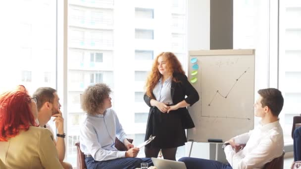 Female boss debating with employees during efficiency charts presentation.