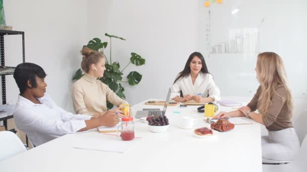 Cheerful young business women work at laptop