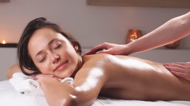 Mladá žena si užívá masáž těla v luxusních lázních